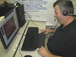 An Employ-Ability Participant uses the screen reading softward JAWS at a computer workstation