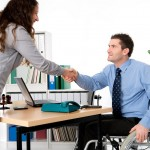 Man in wheelchair shaking hands with employer