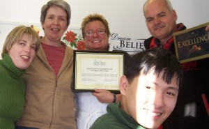 Two literacy participants, Sarah, and Danh help Cheryl present a certificate of appreciation to Banan and Roger Pattison