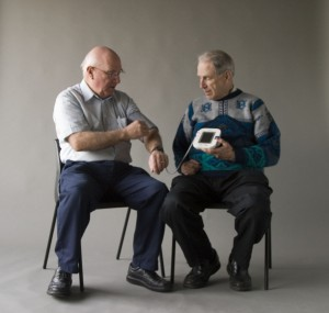 Two senior men sitting in chairs facing one another and looking at a piece of technology