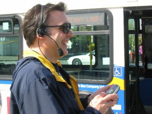 A person wearing a headset and holding cellular phone at a bus stop