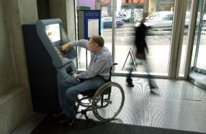A person in a wheelchair using a bank machine