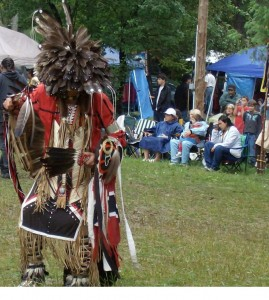 An Algonquin dancer performing in traditional garb
