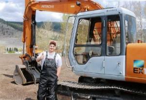 Doug Posing in front of an excavator