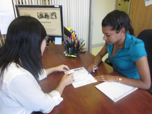 A Working Together staff member working with a participant at a desk
