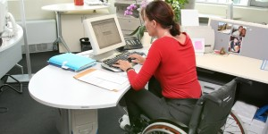 Woman in wheelchair working at a desk