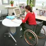 Woman in a wheelchair using a desktop computer