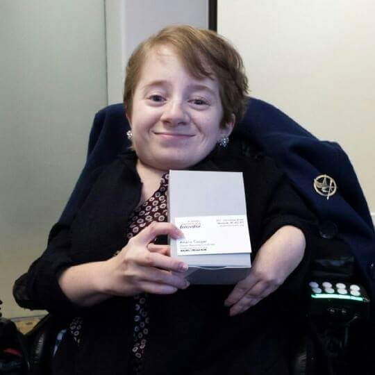 Amelia, a youth in a wheelchair, holding her business card