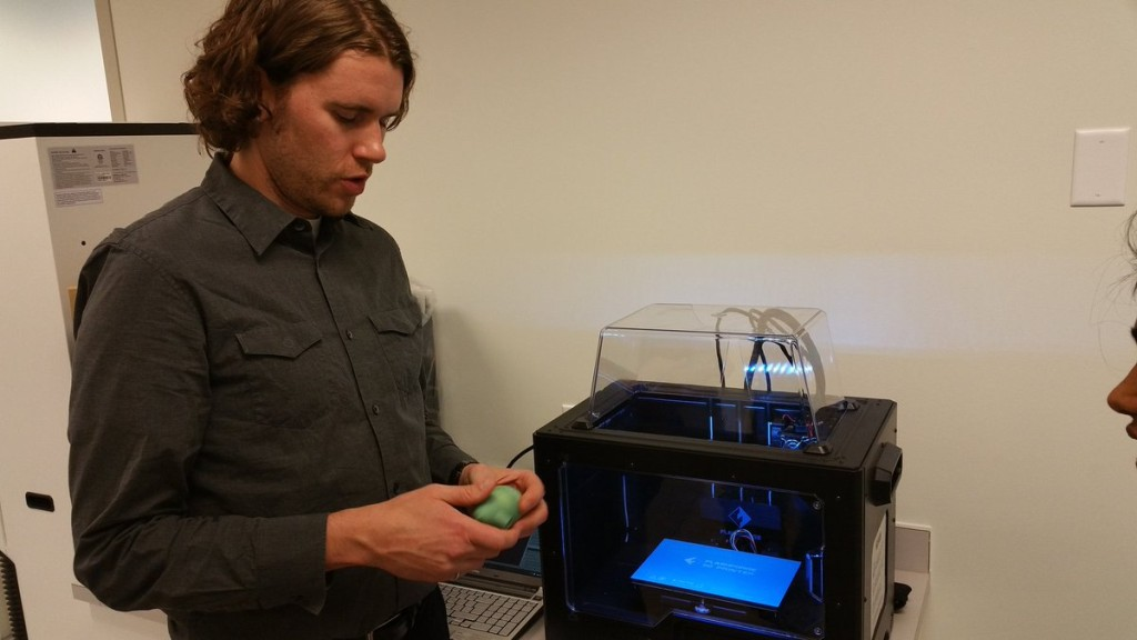 Our engineering student Charles showing off the capabilities of 3D printing to our office staff in front of the Creator Pro