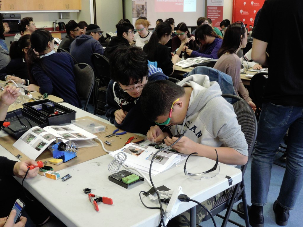 Students working diligently on the soldering process at the beginning of the day.
