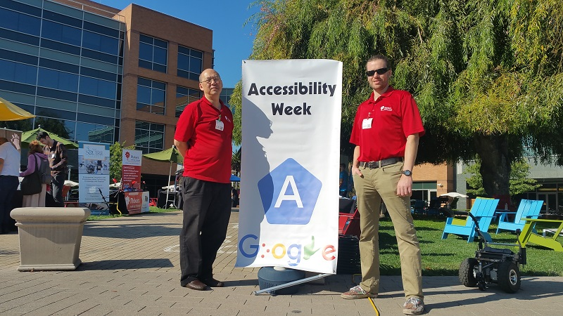 Harry and Charles standing by an Accessibility Week poster