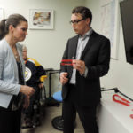 Director of Innovation, Chad Leaman, demonstrates a palm pen holder to Minister Duncan