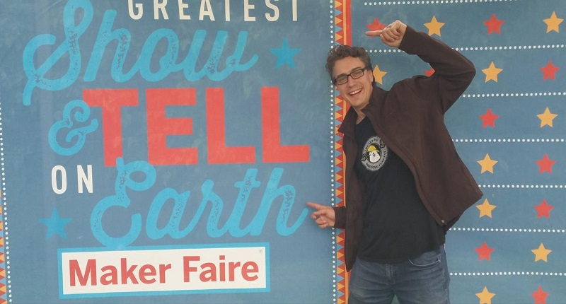 Chad Leaman, Director of Innovation, pointing at a Maker Faire sign