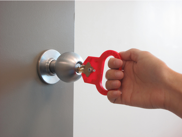 A hand using a key turner to open a door