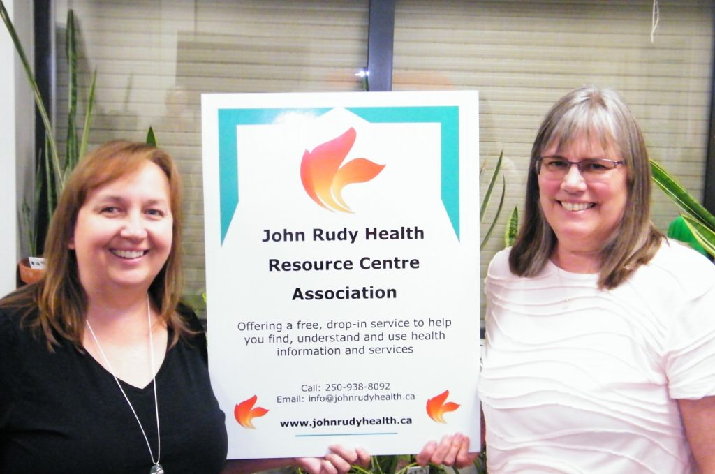 Chantelle (left) and Tracey (right) holding up a John Rudy Health Resource Centre Association banner