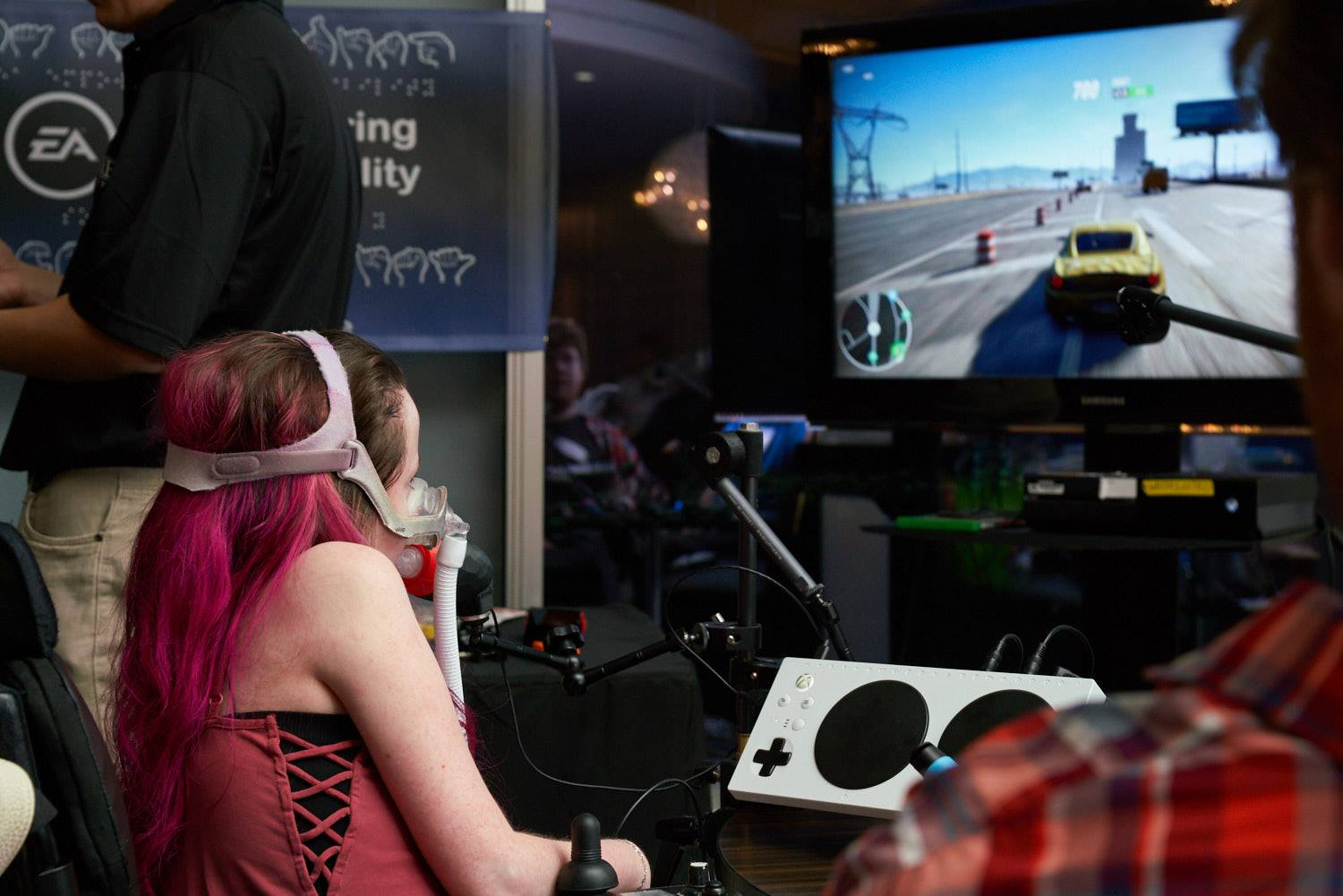 Kaileen plays Need for Speed witht he help of the Xbox Adaptive Controller, our LipSync, and custom buttons attached to her chair