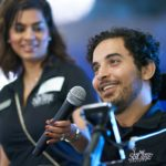 Omar speaking with Shelina Dilgir, Associate Director of Development, holding up the mic