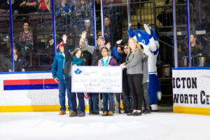 Neil Squire Society receiving their cheque on the ice