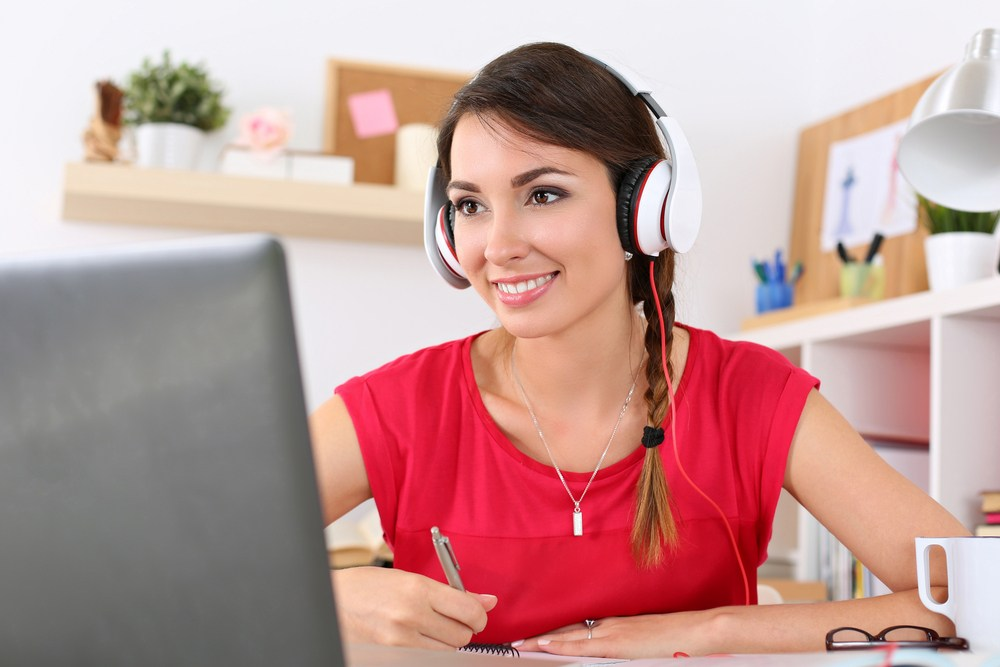 Woman with headphones at a computer