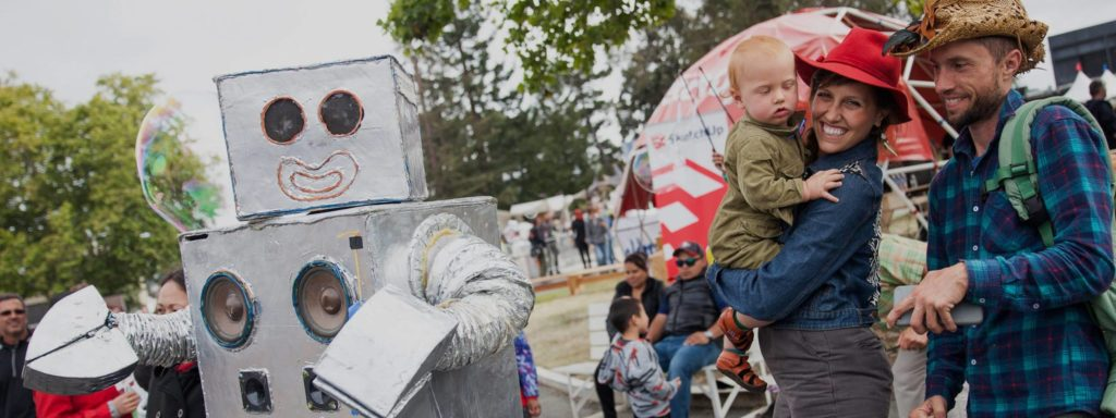 Maker Faire attendees; foreground: a man and a woman with a child, smiling