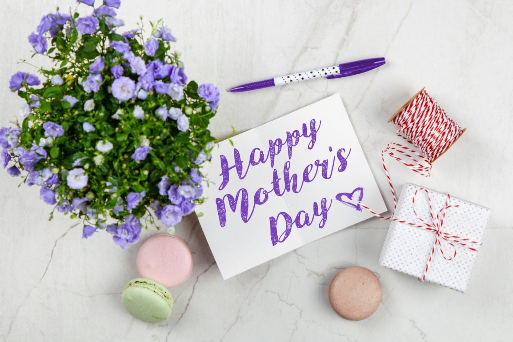 """Happy Mother's Day"" written on a card, with flowers, a present, and macaroons around it"