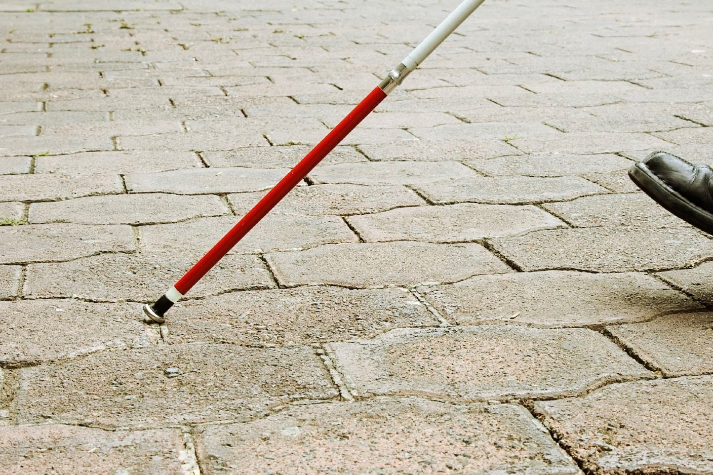 A stock image of a person using a white cane