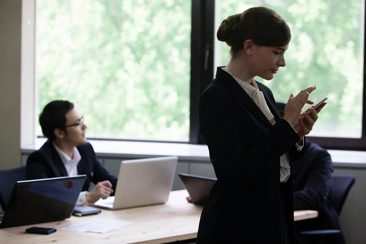 A woman using her phone at work with a man looking away in the background