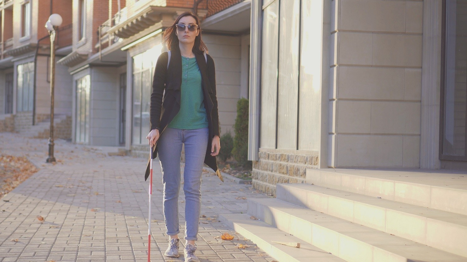 A woman walking on the street using a white cane