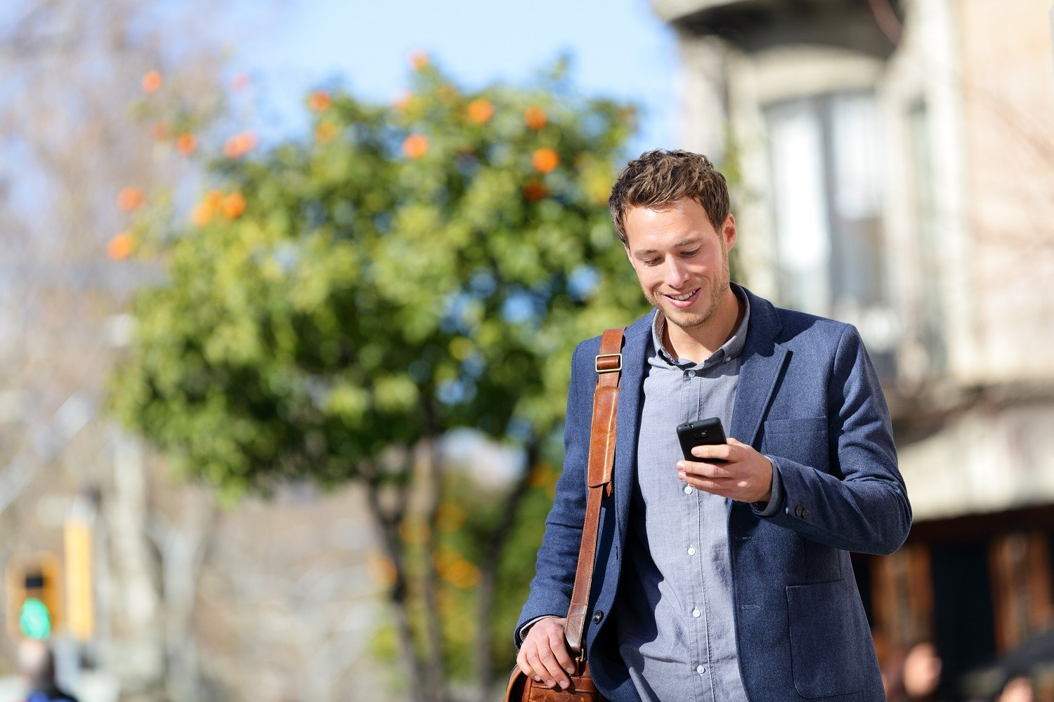 Man walking on the street looking at his phone