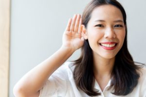 close up young beautiful asian doctor woman smiling with happiness and using hand behind ear to trying listening for deafness concept