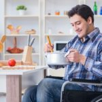 a man in a wheelchair making food