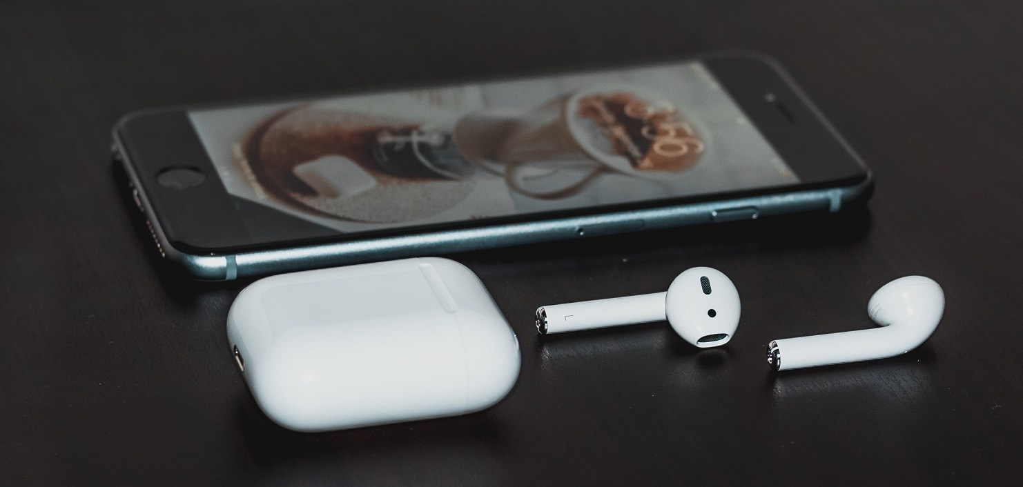 Apple AirPods with an iPhone in the background