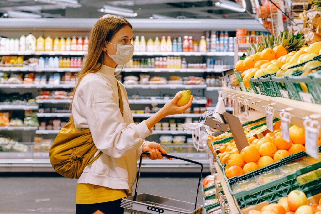 stock image of woman in supermarket holding up fruit