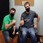 Cody (left) and Josh (right) at work. They are both giving a thumbs-up.