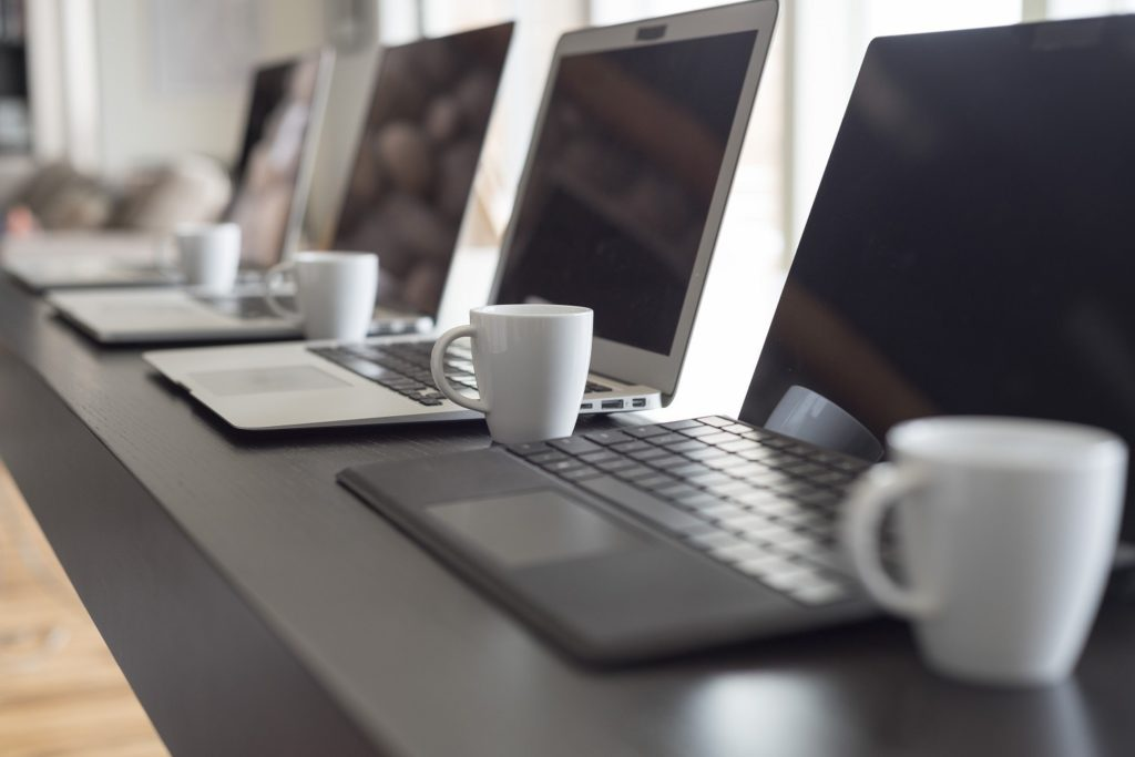 A number of laptops placed in a row on a desk