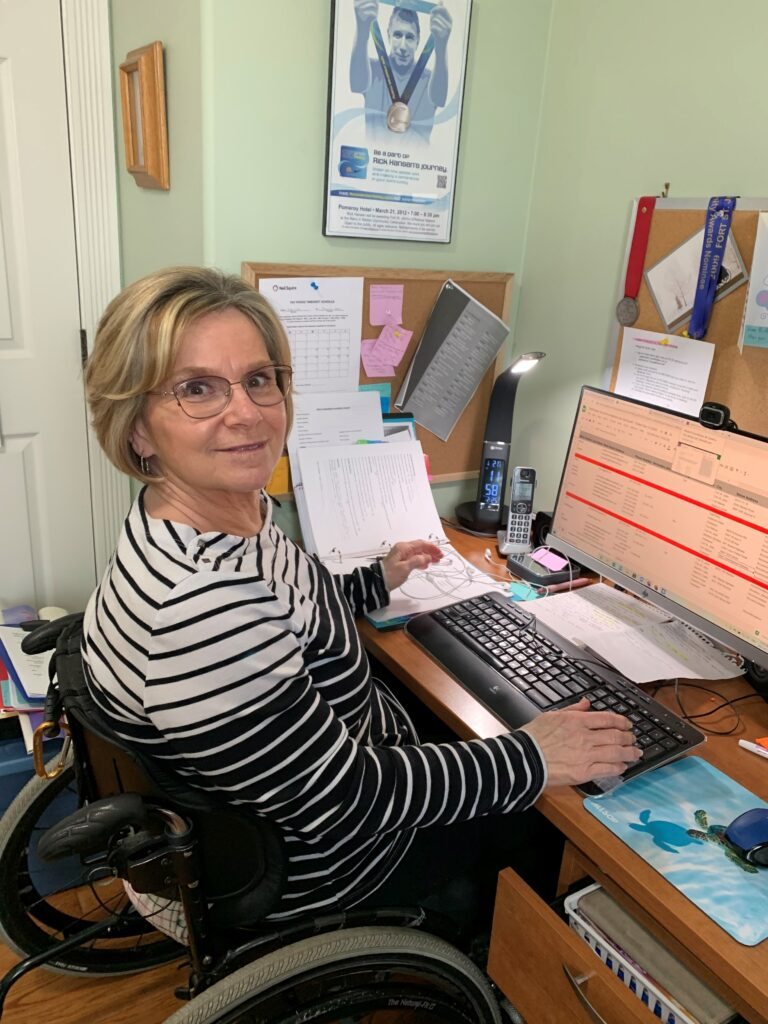 Lori working at her desk, seated in her wheelchair, looking at the camera and smiling
