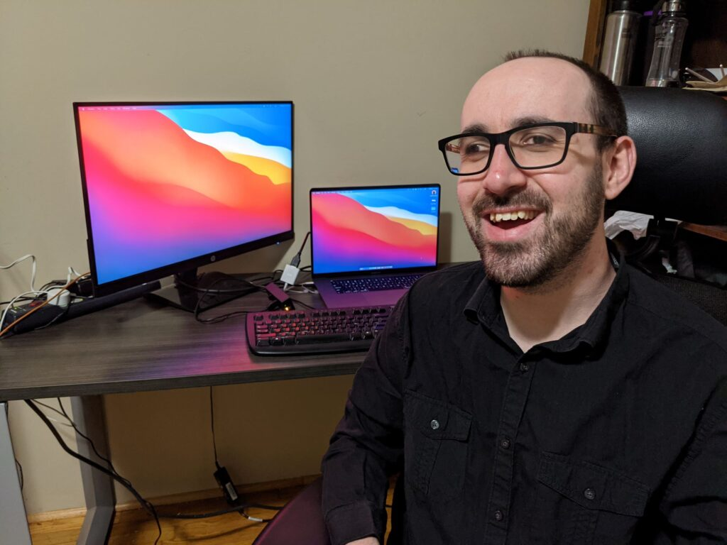 Nate with the equipment he received. He is smiling, seated in an ergonomic chair. Behind him is his desk, with a laptop, keyboard and external monitor