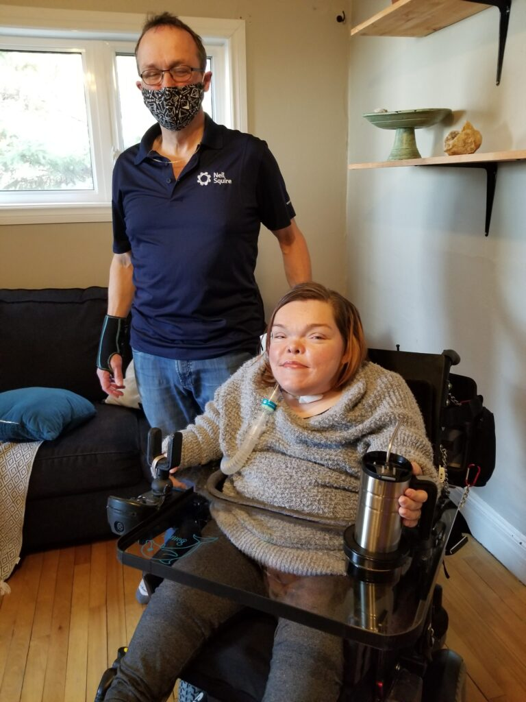 Marc stands next to Bonnie, who is using her wheelchair lap tray to hold a mug.