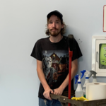Luke at work. He is leaning against the wall, with cleaning equipment next to him