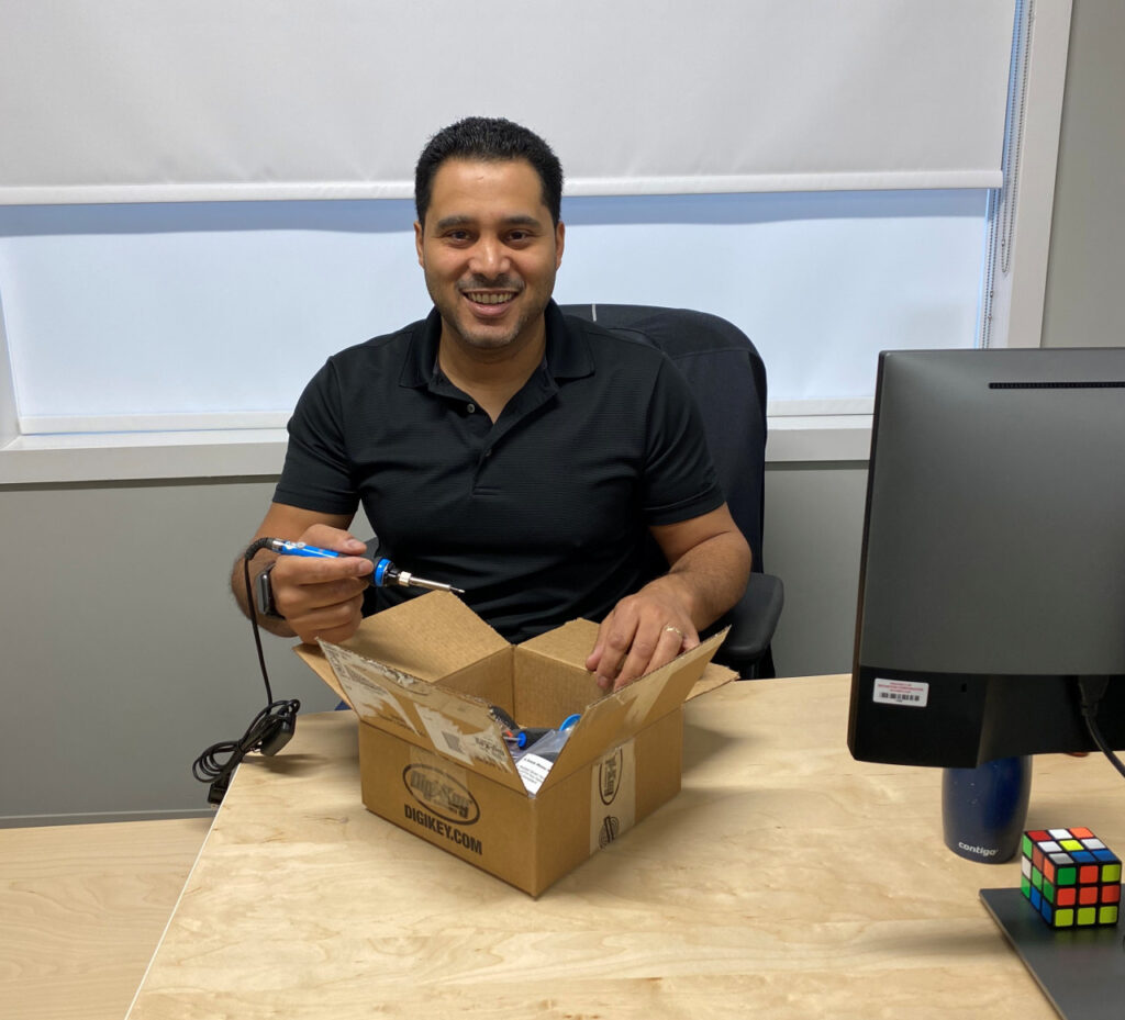 Dan Belhassen, president of Neovation, smiles and holds a soldering iron, as he holds open a box of parts to build a Round Flexure Switch