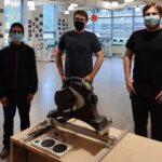 Keith Consolacion, Nicholas Winship, and Scott Beaulieu look over an Arm Cycle Gaming Interface prototype
