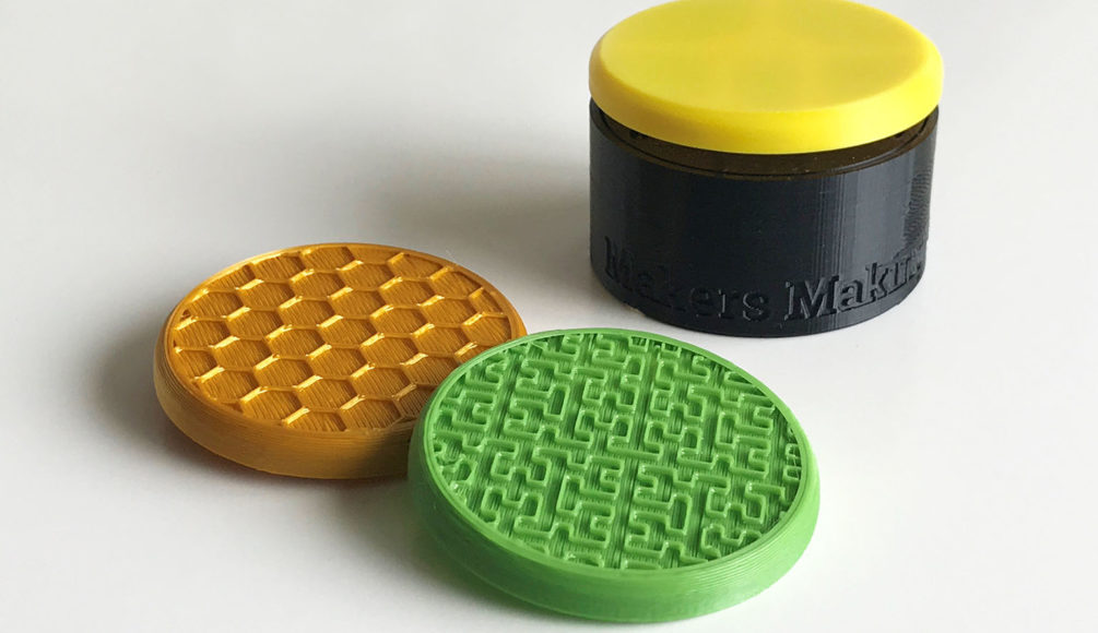A gold honeycomb textured and green maze textured switch tops. In the background is a yellow round flexure switch