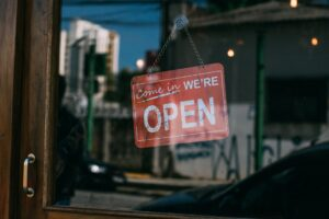 """A storefront with the sign """"Come in, we're open"""""""