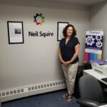 Staff member Tracey posing and smilin next to a Neil Squire banner, with a Neil Squire logo on the wall behind