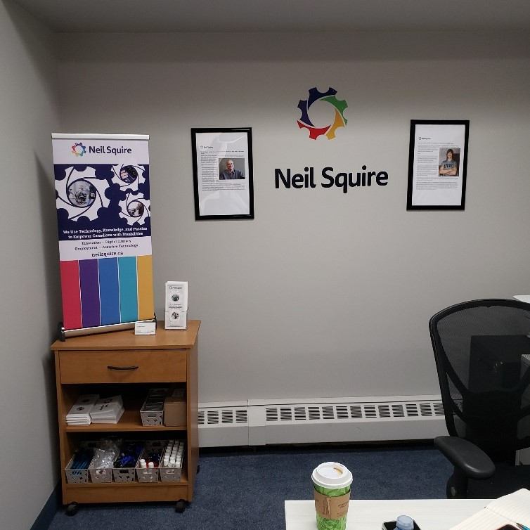 A small table with a Neil Squire banner on it. On the wall is a Neil Squire logo and two framed articles: one of Neil Squire, the other of Gary Birch