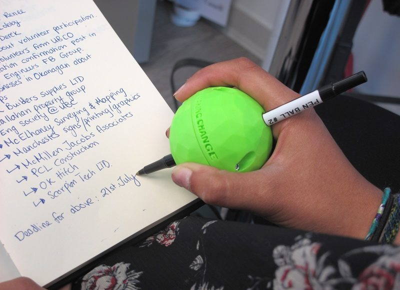 A user using the 3D Printed Pen Ball Holder to write on a piece of paper with ease