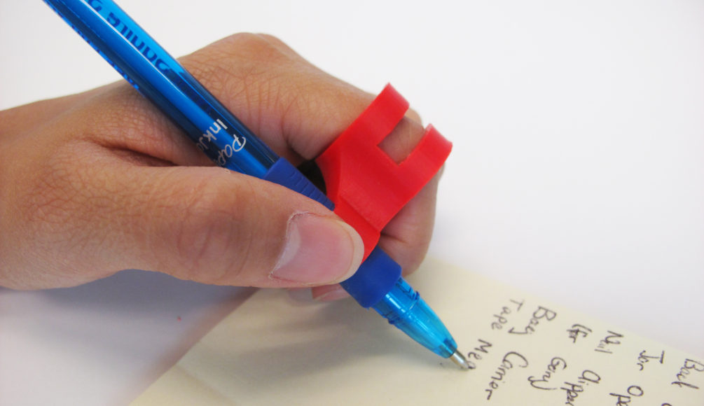 A user using the 3D Printed finger pen holder to write with ease