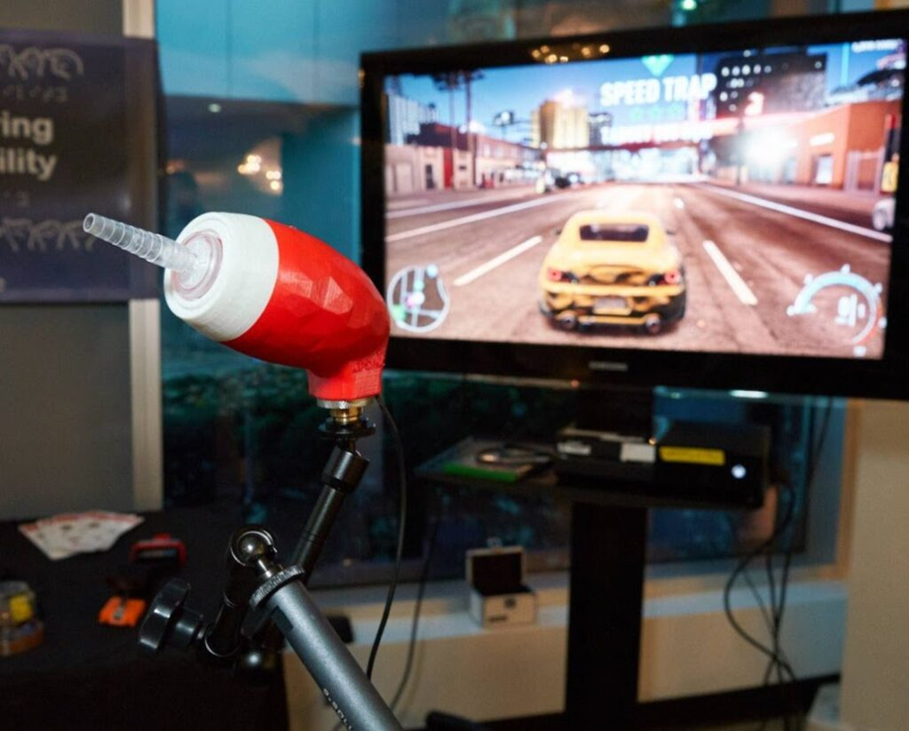 A LipSync is mounted in front of a TV which is a displaying a racing video game