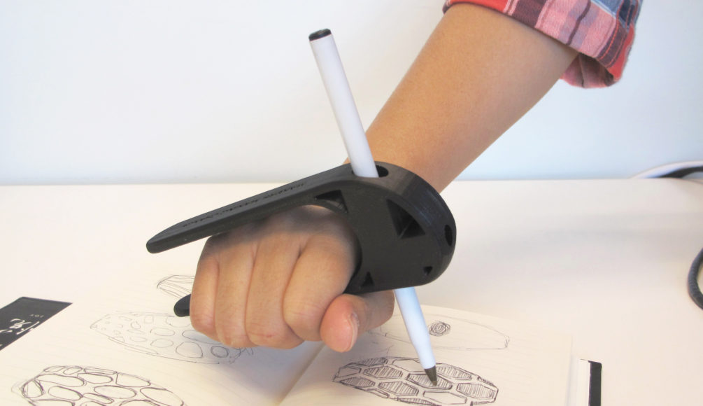 A user using the 3D Printed Palm Pen Holder to draw on a piece of paper with ease