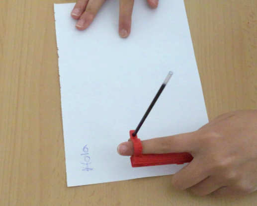 """A person uses the Arm-mounted Pen Holder to write """"Hola"""" on a piece of paper twice"""